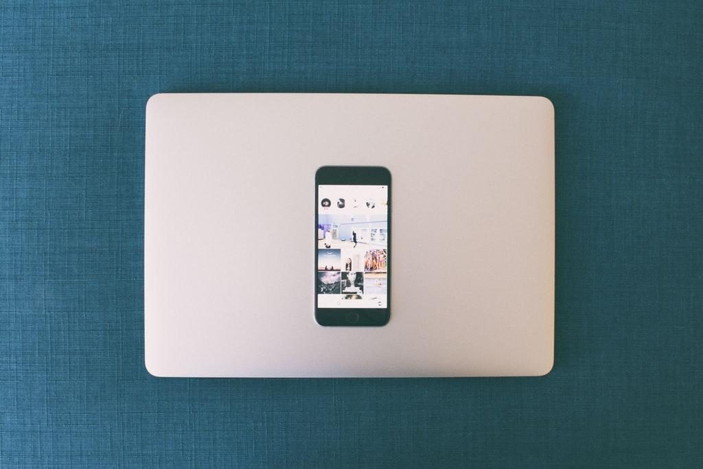 Instagram feed on smartphone on top of closed laptop - Build Your Brand On Instagram