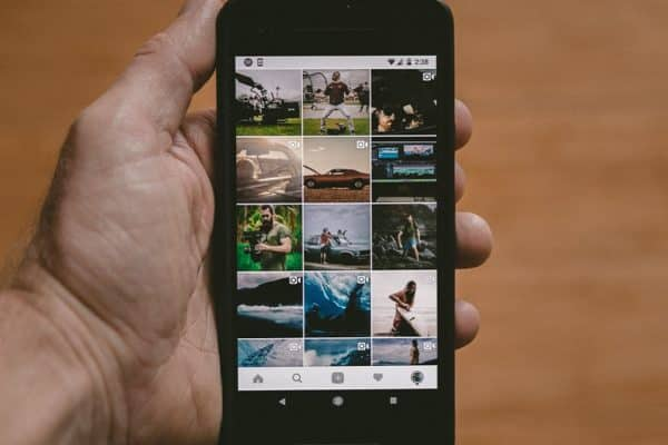 Instagram feed on phone in man's hand - Build Your Brand on Instagram