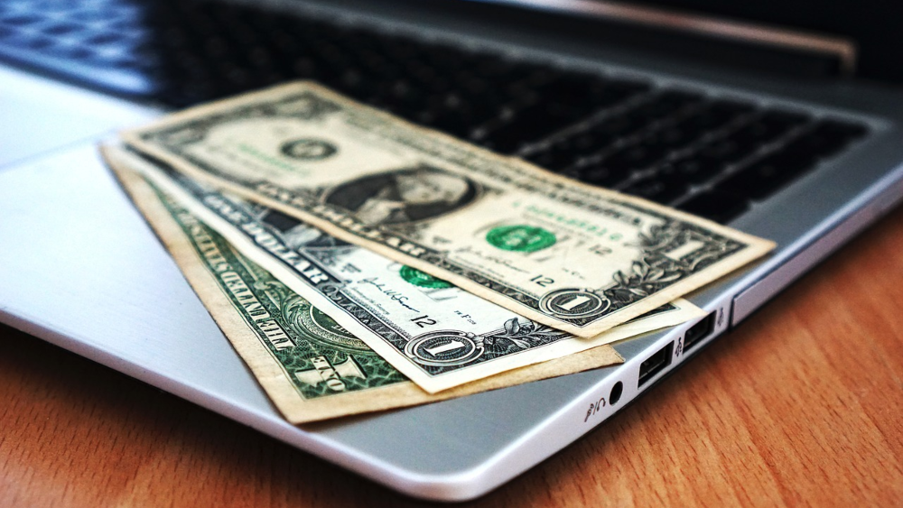 Dollar bills on laptop keyboard - 11 Ways to Make Money Online