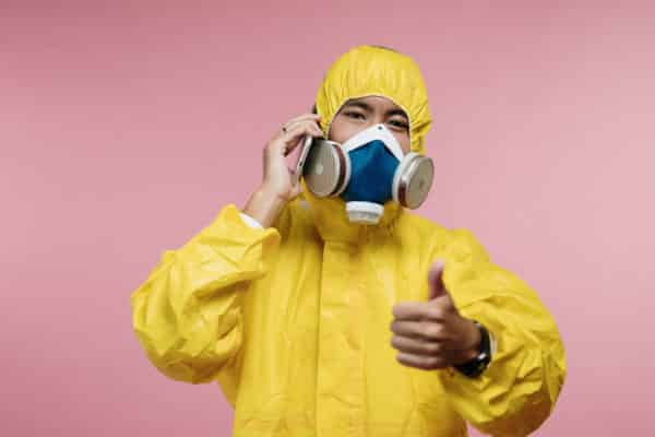Person in protective suit talking on phone with thumbs up - How to Start a Business While Quarantining