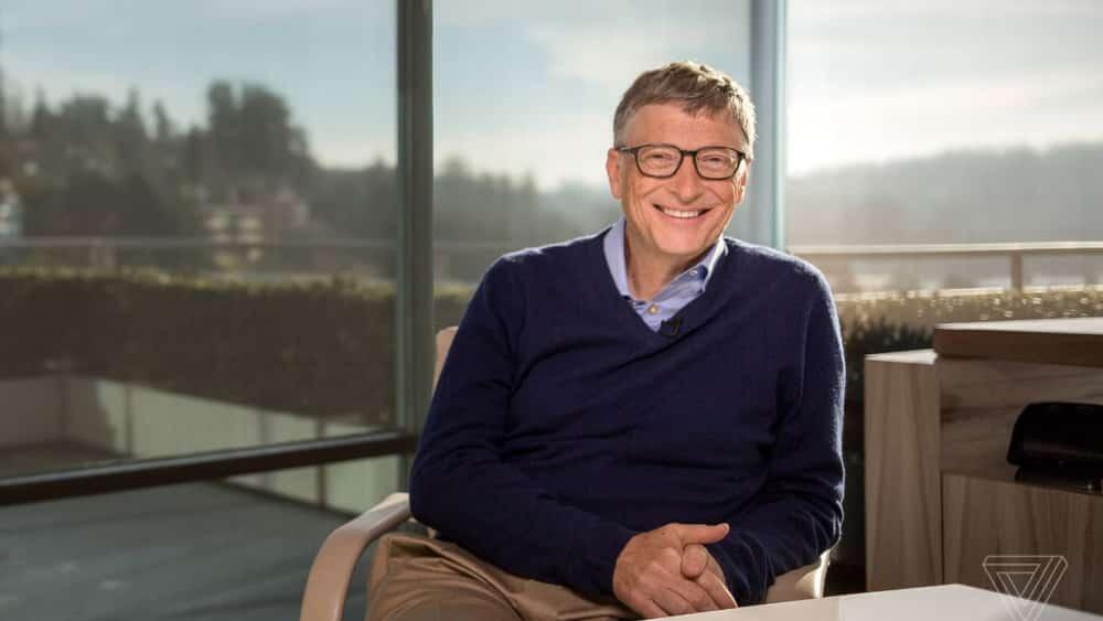 Bill Gates smiling at desk - 6 Valuable Branding Lessons from Millionaire Entrepreneurs