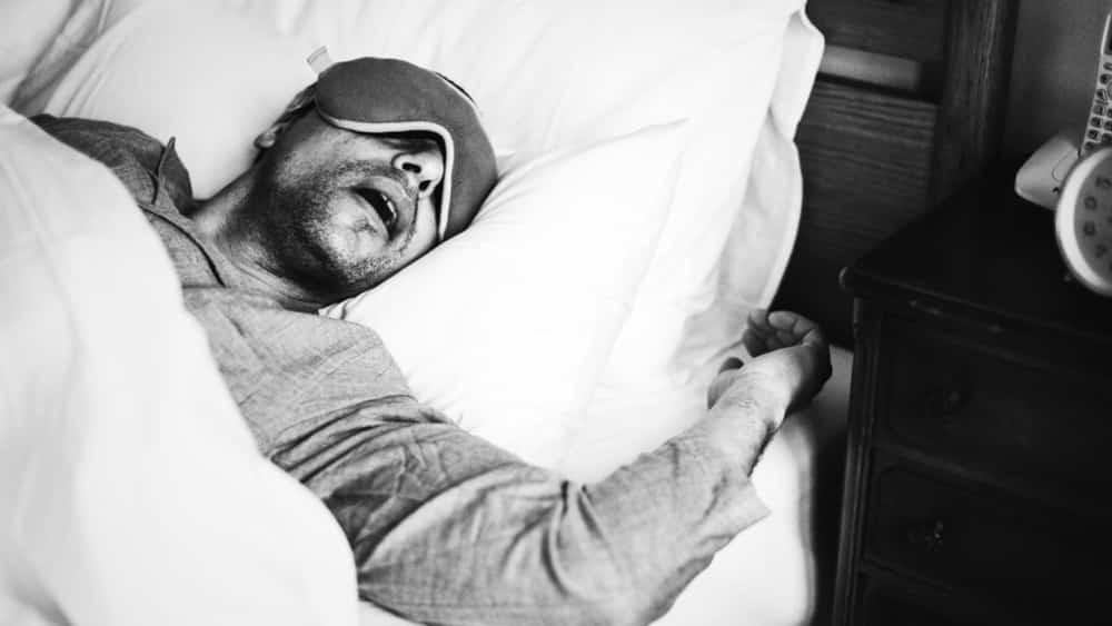 Creative professional sleeping with eye mask to improve productivity during the day