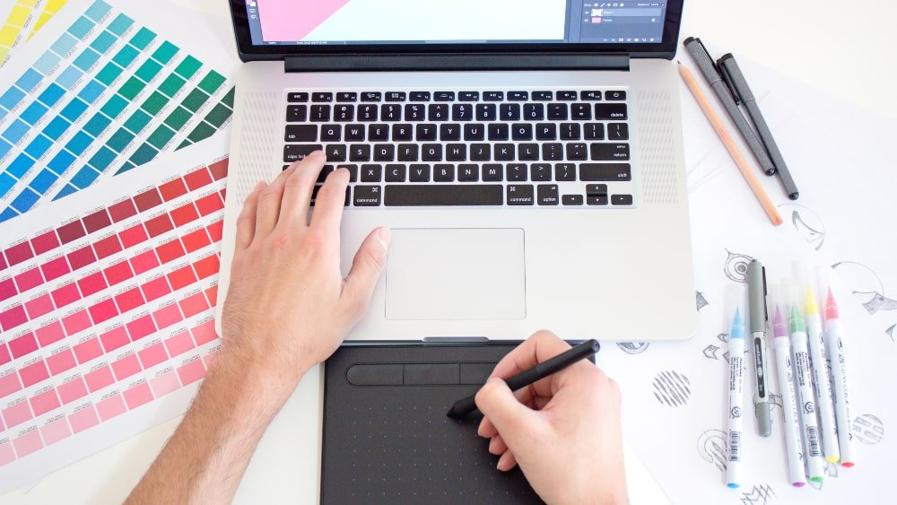 Graphic designer working on drawing pad with colours