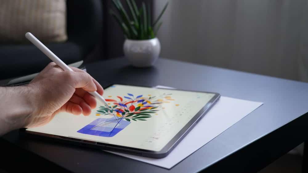 Graphic designer illustrating flowers on tablet