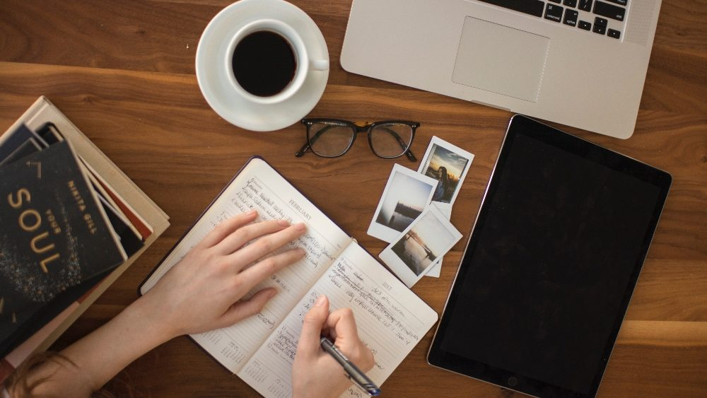 Woman writing copy in notebook - 10 Copywriting Lessons From John Carlton That'll Sell More Stuff