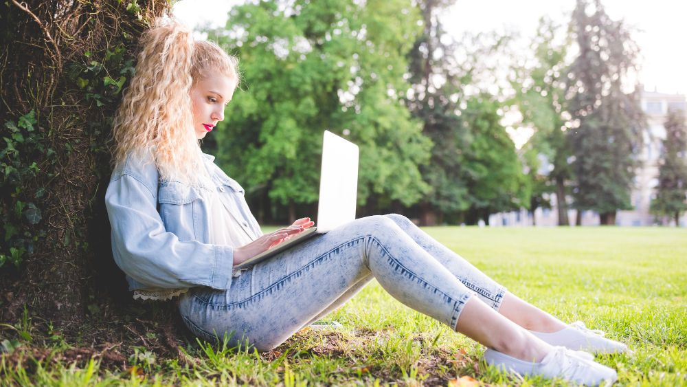 Woman using laptop on grass reading personalised content