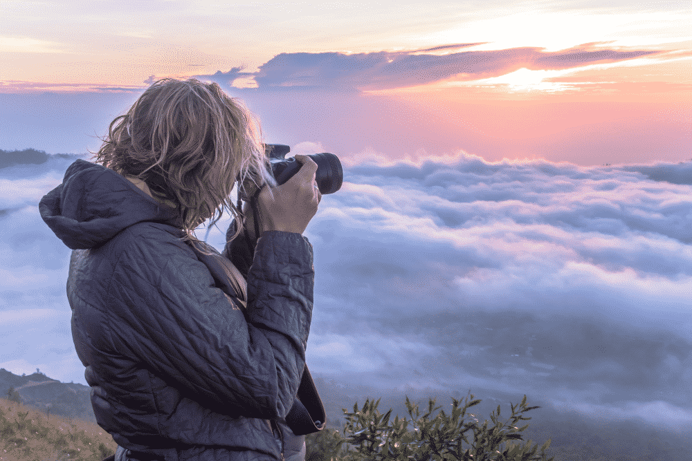 Photographer taking photos above clouds