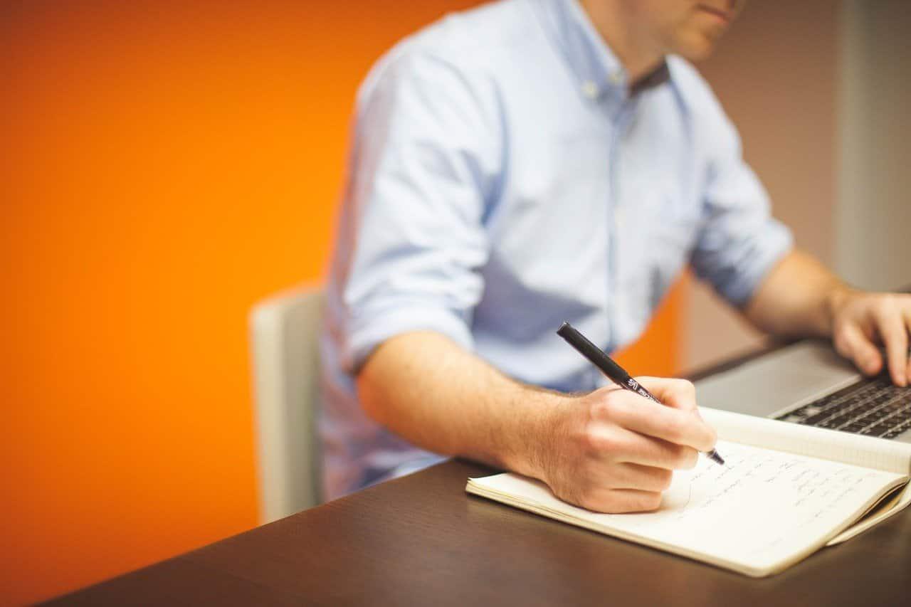 Man writing on notepad taking branding course