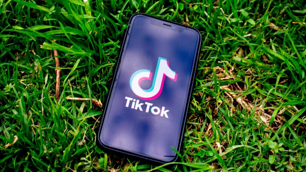 TikTok logo on iPhone on grass background - 5 Ways For Brands To Use TikTok For Growth