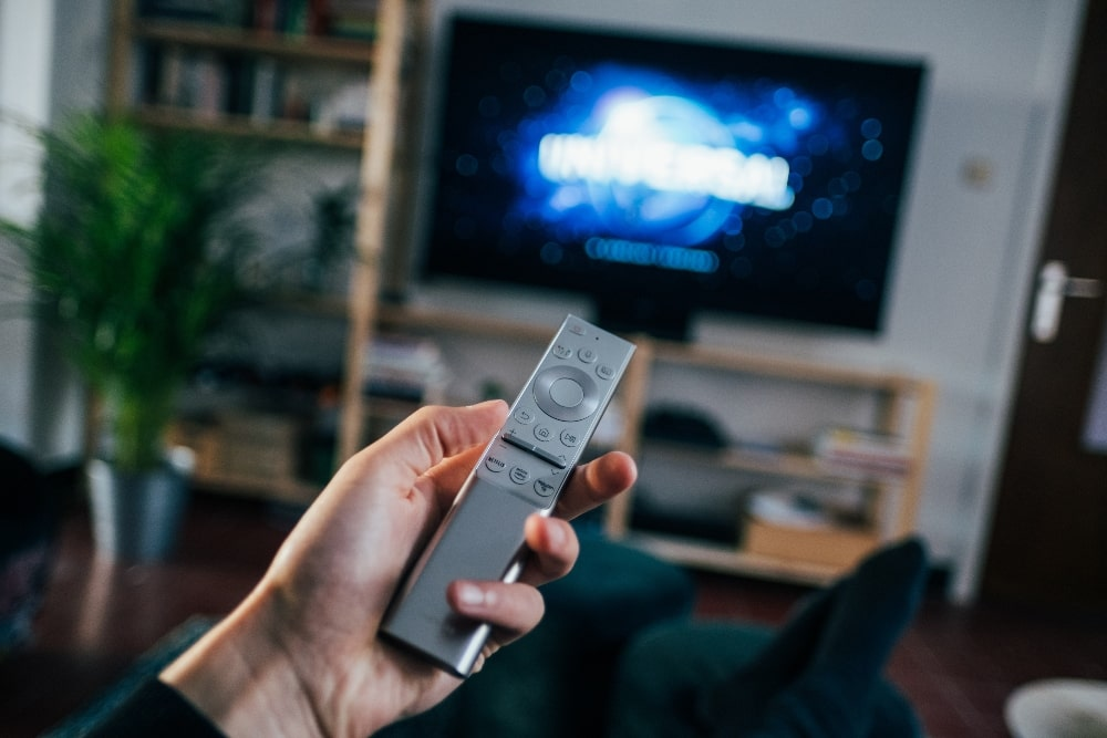 Man holding remote watching TV with captions