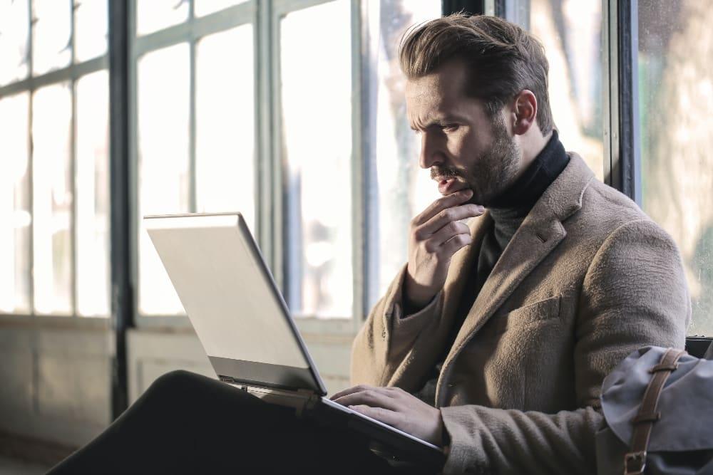 Man experiencing analysis paralysis using laptop